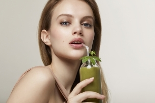 girl drinking a green cocktail